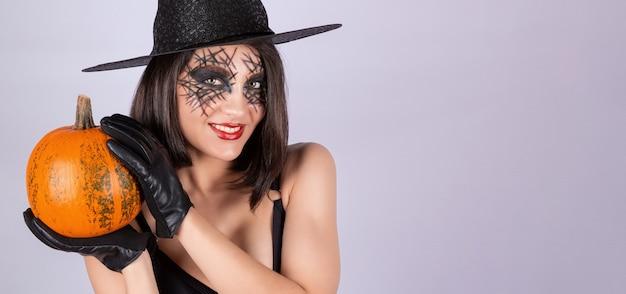 Een meisje met zwarte handschoenen houdt een pompoen vast voor halloween