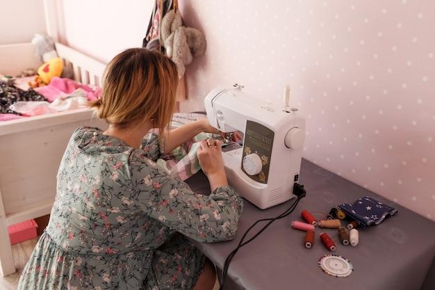 Een meisje naait thuis op een naaimachine. achteraanzicht is een favoriete hobby. eigen productie van kleding.
