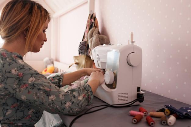 Een meisje naait thuis op een naaimachine. achteraanzicht is een favoriete hobby
