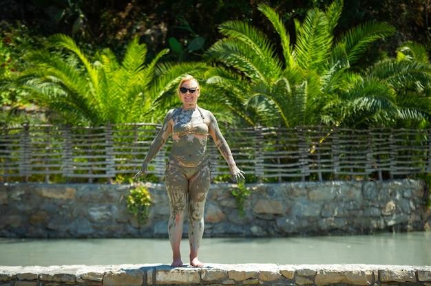 Een meisje neemt een modderbad in een resort in turkije. verbetering van de gezondheid in therapeutische modder.