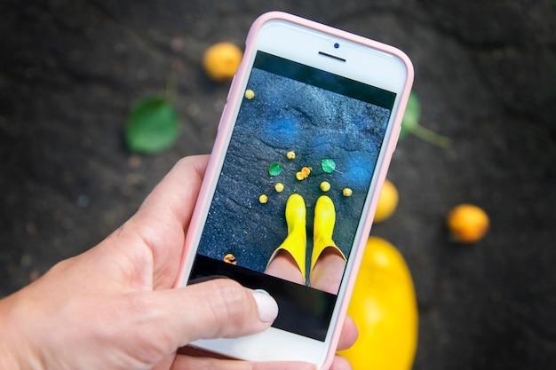 Een meisje neemt foto's van haar benen in gele laarzen aan de telefoon. een zomerregenconcept.