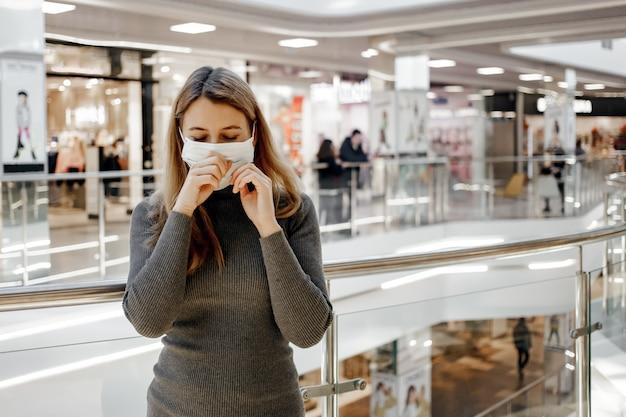 Een meisje niest in een beschermend masker in een winkelcentrum