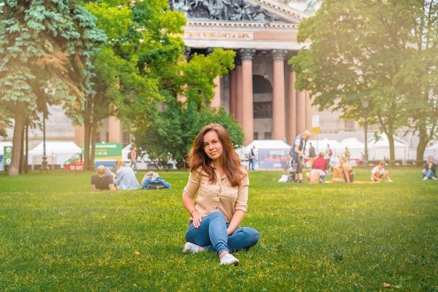 Een meisje ontspant op het gras in het centrum van sint-petersburg, voor de izaäkkathedraal