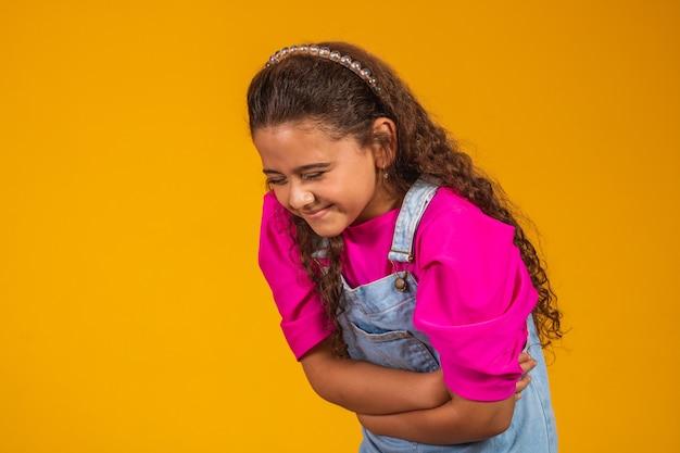 Een meisje op een gele achtergrond heeft buikpijn. hand in hand op buik en lijden.