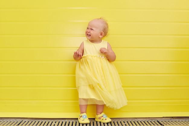 Een meisje op een gele muur in een gele jurk. kopieer ruimte