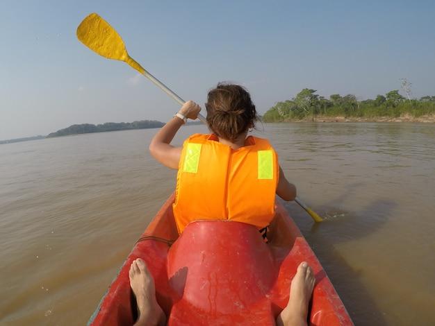 Een meisje op een kanotocht langs de rivier de madre de dios in puerto maldonado, peru