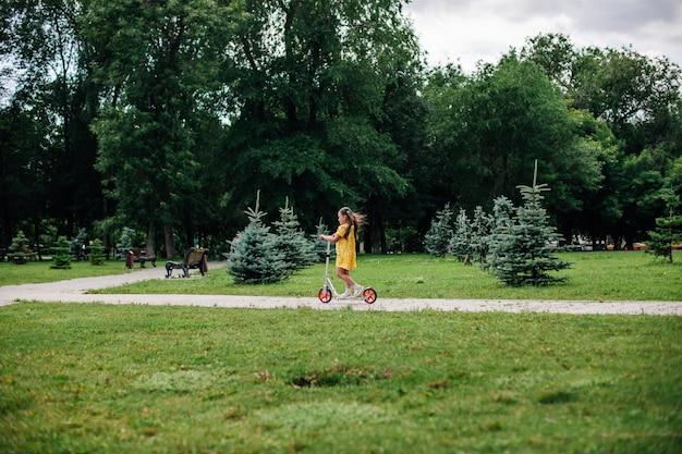 Een meisje op een scooter een nuttige fitnesswandeling door het bos met haar familie tijdens een zomerweekend
