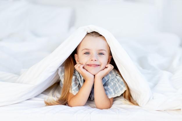 Een meisje op het bed thuis op een wit katoenen bed ligt onder een deken of is 's ochtends wakker geworden en lacht zoet