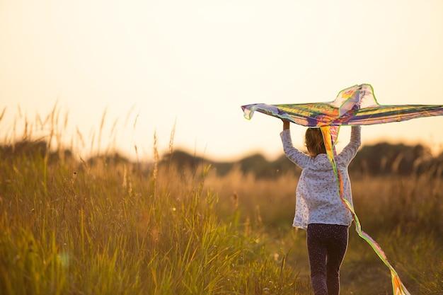 Een meisje rent een veld in met een vlieger, leert het te lanceren. outdoor entertainment in de zomer, natuur en frisse lucht. jeugd, vrijheid en zorgeloosheid. een kind met vleugels is een droom en een hoop.
