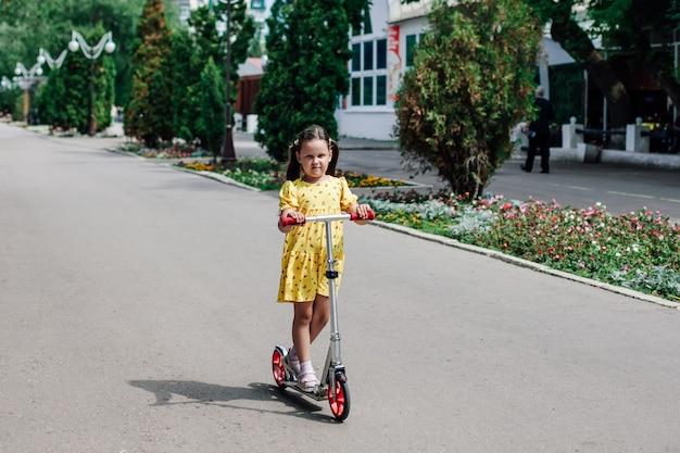 Een meisje rijdt op een scooter een familiewandeling op een zomerdag op scooters een gezonde levensstijl en recreatie