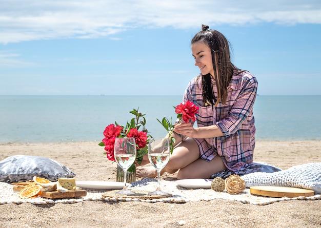Een meisje rust op het strand. een romantische picknick aan de zanderige kust van het strand. het concept van zomervakantie.