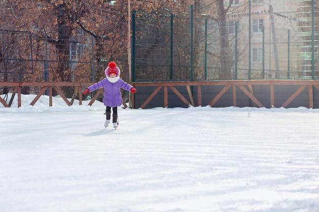 Een meisje schaatst in de winter op een ijsbaan. ijsbaan op de binnenplaats van de stad. kind leert schaatsen