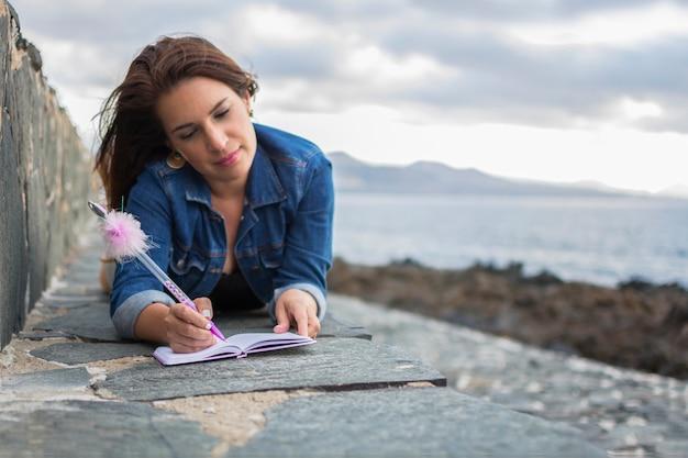 Een meisje schrijft buitenshuis, vlakbij de zee, in haar roze notitieboek met een pen met een hele mooie pompon.