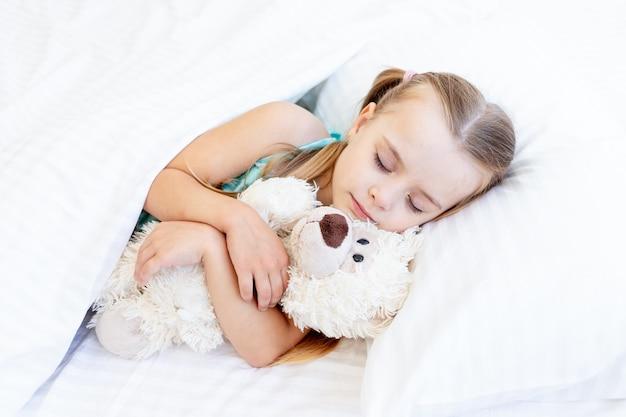 Een meisje slaapt thuis op een bed op een wit katoenen bed, knuffelt een teddybeer in haar handen en lacht liefjes in haar slaap