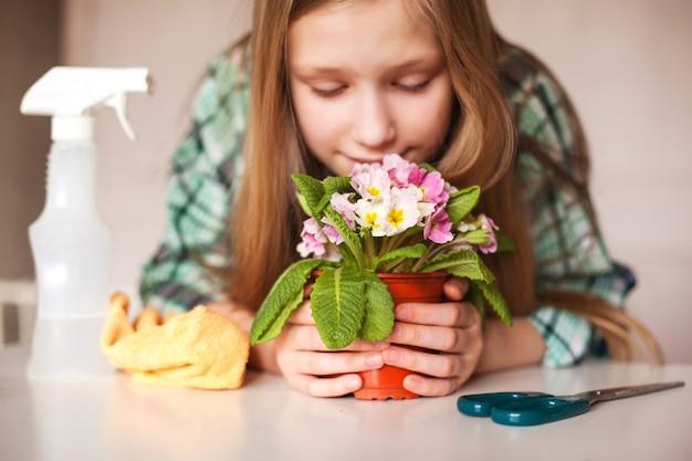 Een meisje snuift aan een bloem en zorgt voor planten in haar huis, close-up