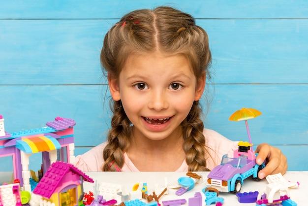 Een meisje speelt constructeur op een blauwe achtergrond.