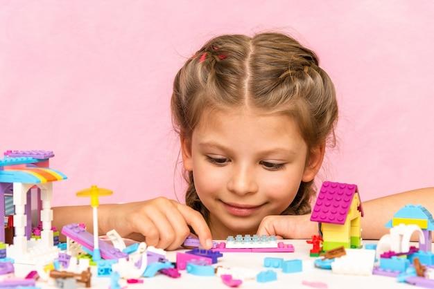 Een meisje speelt een constructeur op een roze ondergrond