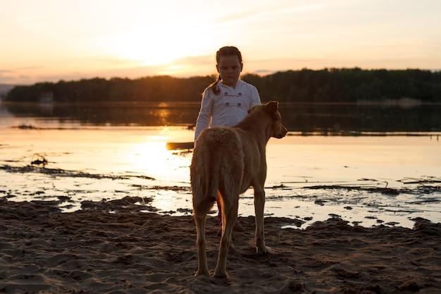 Een meisje speelt met een hond op een zandstrand bij de rivier bij zonsondergang.
