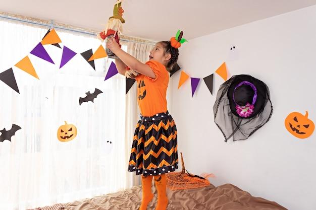 Een meisje speelt met een opgezette vogelverschrikker, springt op een bed en draagt een pompoenkostuum