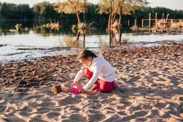 Een meisje speelt met zand op een zandstrand aan de rivieroever tijdens zonsondergang.
