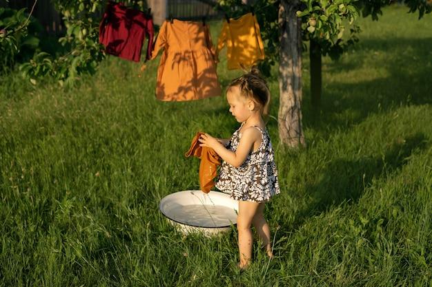 Een meisje spettert in een bak met zeepsop, wast haar kleren en hangt de was op