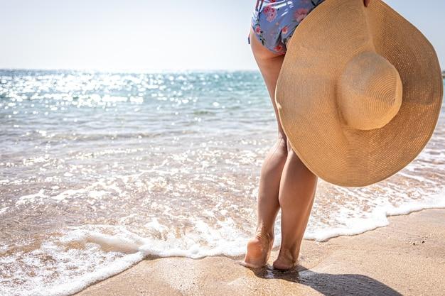Een meisje staat aan de zanderige kust met een hoed in haar hand.