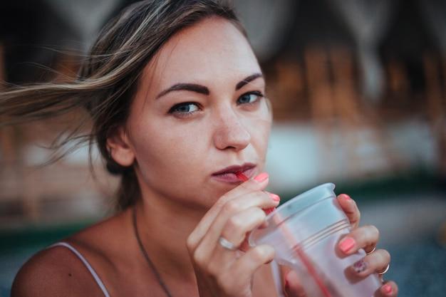 Een meisje staat bij de zee en drinkt een cocktail