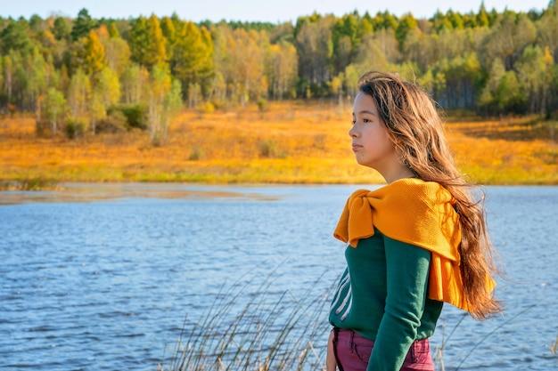 Een meisje staat bij het meer het meisje kijkt naar de herfstnatuur herfstboskleuren en het meisje