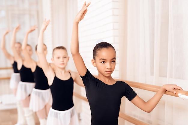 Een meisje staat in de studio en oefent een oefening.