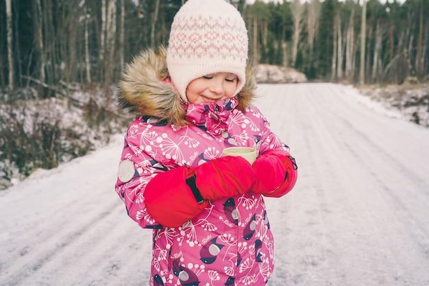 Een meisje staat in de winter op straat en drinkt thee uit een thermoskan.