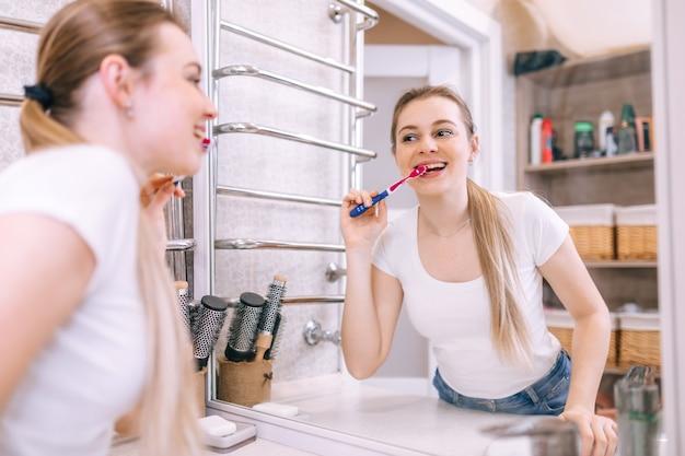 Een meisje staat in een moderne badkamer met een roze tandenborstel in haar handen. poets uw tanden dagelijks 's ochtends en' s avonds voor een goede mondgezondheid en sterke tanden.