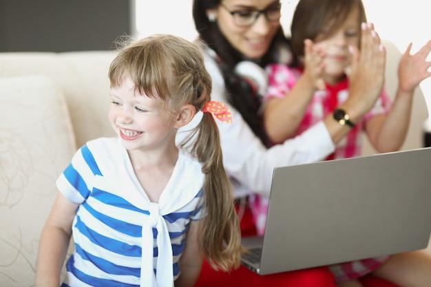 Een meisje staat naast haar moeder op de bank met een babysitter op de laptop en communiceert