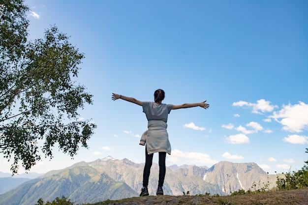 Een meisje staat op de top van een berg met haar handen omhoog.