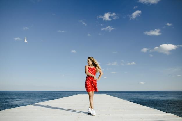 Een meisje staat op een ligplaats en kijkt naar zee