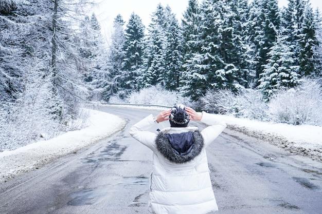 Een meisje staat op een verlaten weg rond hoge bomen, close-up. mensen op een winter weg. dromen van reizen. winterreis