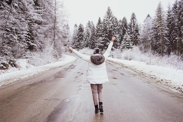 Een meisje staat op een verlaten weg rond hoge bomen