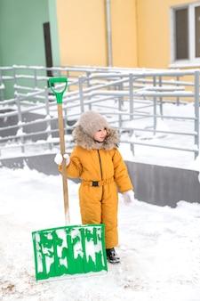 Een meisje staat op een winterdag buiten het huis met een grote schop om sneeuw te ruimen