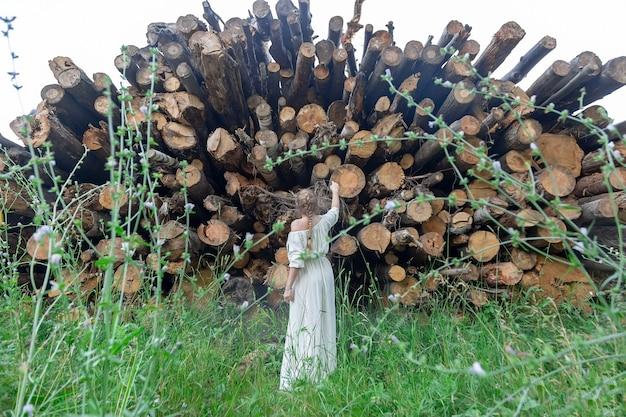 Een meisje staat voor gekapte bomen en kijkt er met spijt naar zorg voor en red de natuur