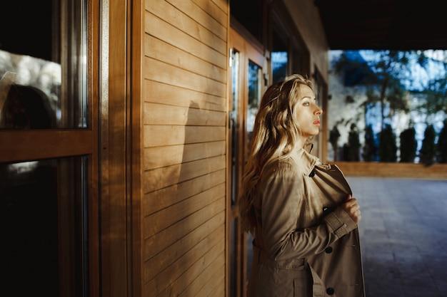 Een meisje staat zijwaarts bij een muur en kijkt in de verte