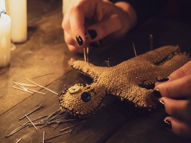 Een meisje steekt pinnen in een voodoo-pop gemaakt van jute, close-up. de voodoo-pop in een mysterieus kaarslicht.