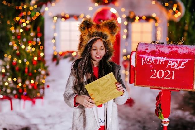 Een meisje stuurt een brief naar de kerstman in een brievenbus