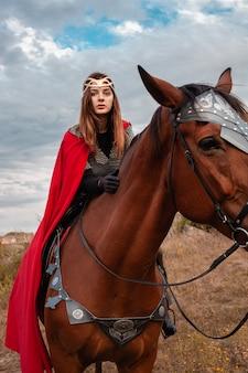 Een meisje te paard tegen de hemel. een mooie vrouw in het kostuum van de krijgerskoningin.