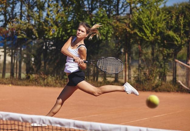 Een meisje tennissen op de baan op een mooie zonnige dag