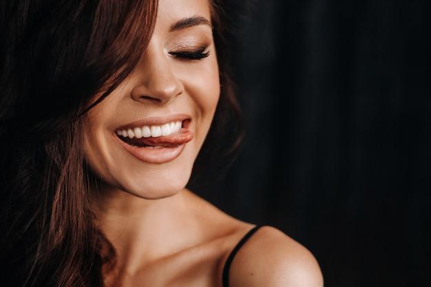 Een meisje toont haar tong in de studio op een zwarte achtergrond.