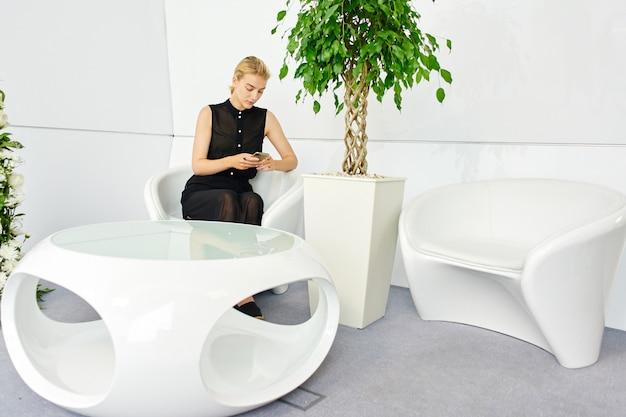 Een meisje uit de toekomst zit op de achtergrond van het futuristische interieur van het gebouw en maakt gebruik van 5g mobiel internet