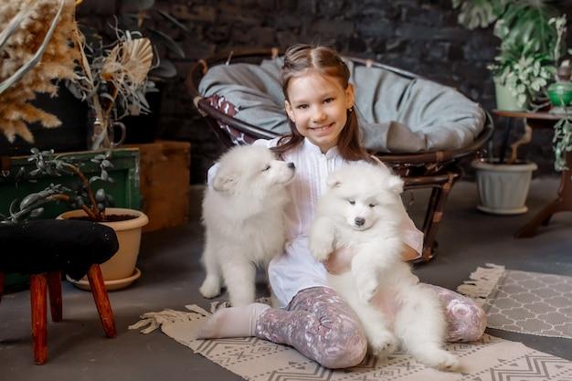 Een meisje van 8 jaar speelt met een huisdier - thuis een witte pluizige puppy