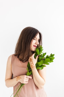 Een meisje van europese uitstraling poseert in een licht interieur, het meisje houdt de bladeren vast