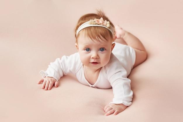 Een meisje van vier maanden ligt op een lichtroze achtergrond