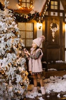 Een meisje van vijf of zes jaar in winter roze kleding en ugg laarzen staat in de buurt van de kerstboom