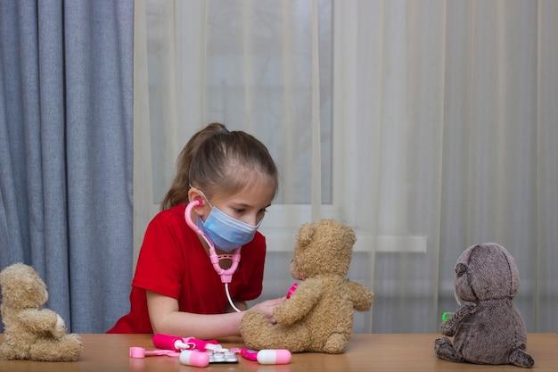 Een meisje van voorschoolse leeftijd met een medisch masker dat in een ziekenhuis speelt met speelgoed luistert naar een fanndoscope